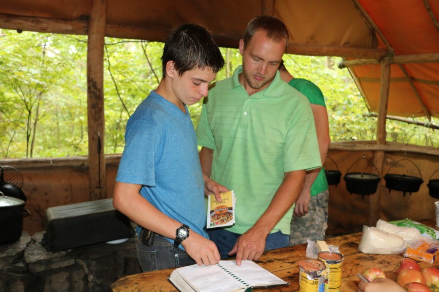 Counselor and camper with tent rope